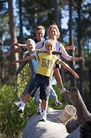 Two generation family walking in line on log, arms outstretched, smiling, front view, portrait