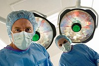 Surgeons in surgical masks standing in operating theatre, low angle view, personal perspective