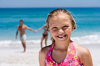 Girl 9-11 standing on beach, smiling, portrait, parents in background, focus on foreground