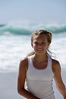Teenage girl 13-15 standing on beach, smiling, front view, portrait
