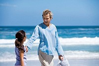 Grandmother walking with granddaughter 7-9 on beach near water's edge, smiling