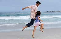 Father and daughter 6-8 skipping on beach near water´s edge, side view