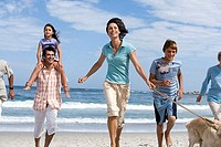 Multi-generational family walking dog on beach, girl 6-8 on father's shoulders, smiling