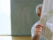 Senior man reading financial newspaper, face obscured
