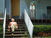 Senior couple relaxing at home, woman standing on veranda, man sitting on steps, smiling