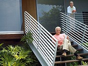 Senior couple relaxing at home, woman standing on veranda, man sitting on steps, smiling, portrait