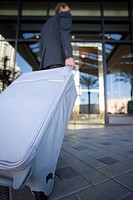 Businessman walking towards hotel door with luggage, rear view, low angle view