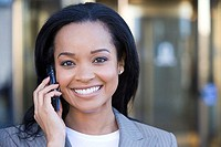 Businesswoman using mobile phone, outdoors, smiling, close-up, front view, portrait