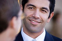 Businessman talking to colleague, smiling, close-up differential focus