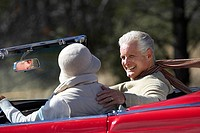 Senior couple driving along country road in red convertible car, smiling, side view