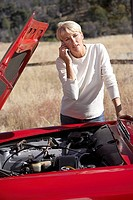 Woman standing beside red convertible car with engine trouble, using mobile phone