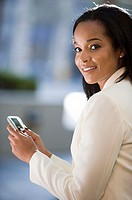 Businesswoman holding personal electronic organiser, smiling, side view, portrait