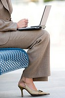 Businesswoman in suit and high heels using laptop on pavement bench, low section, profile