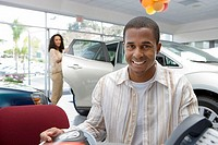 Man sitting at desk in car showroom, looking at brochure, woman beside new car, smiling, portrait