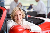 Salesman with customer in car showroom, woman in red convertible in foreground, smiling, portrait