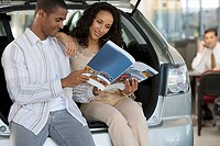 Salesman in car showroom, focus on couple looking at brochure beside new hatchback in foreground
