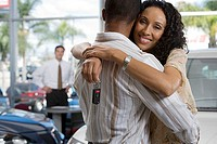 Salesman in car showroom, focus on couple embracing in foreground, woman holding key, smiling