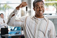 Salesman in car showroom, focus on male customer holding key in foreground, smiling, portrait