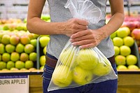 Woman standing in supermarket, holding bag of apples, mid-section, front view