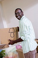 Man moving house, holding cardboard box in living room, smiling, side view, portrait tilt