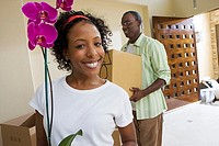 Couple moving house, man carrying box in hallway, woman holding pot plant, smiling, portrait