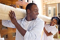 Couple moving house, carrying rolled-up carpet on shoulders through doorway, smiling