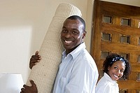 Couple moving house, man holding rolled-up carpet, woman standing in doorway, smiling, portrait