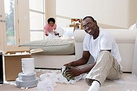 Couple moving house, woman with lamp, focus on man unpacking glassware in living room, smiling, portrait