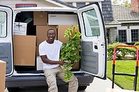 Man moving house, sitting in rear of van with pot plant, smiling, portrait