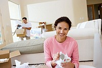 Couple moving house, man unpacking lamp, focus on woman unwrapping crockery in living room, portrait