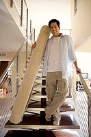 Man moving house, standing at bottom of staircase with rolled-up carpet, smiling, portrait