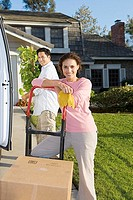 Couple moving house, man beside van with pot plant, woman leaning on hand dolly, smiling, portrait