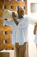 Couple moving house, carrying rolled-up carpet on shoulders through doorway, man smiling, side view