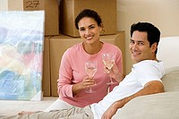 Couple moving house, sitting on floor in living room, holding glasses of wine, smiling, portrait
