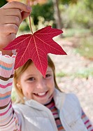 Girl 7-9 holding aloft red maple leaf in park in autumn, smiling, close-up, portrait