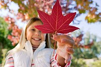 Girl 7-9 holding red maple leaf in park in autumn, smiling, close-up, low angle view