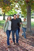 Senior couple walking with adult son and daughter-in-law in park in autumn, smiling