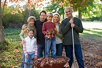 Multi-generational family standing in garden in autumn, boy 6-8 standing in wheelbarrow, smiling, portrait