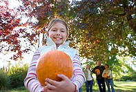 Multi-generational family standing in garden in autumn, focus on girl 6-8 holding pumpkin, smiling, portrait