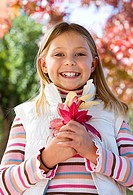 Girl 7-9 standing in autumn garden, holding red maple leaf, smiling, close-up, portrait