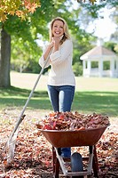 Woman collecting autumn leaves in garden, standing beside full wheelbarrow, leaning on rake, smiling, portrait