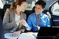 Businessman and woman shaking hands in the back-seat of car, man using laptop, woman with contract