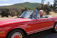 Mature couple driving in red convertible car along country road, smiling, side view