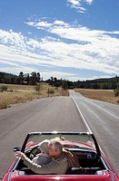 Mature couple sitting in red convertible car on country road, woman driving, man pointing at scenery, rear view