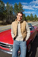 Man standing in front of red convertible car on country road, smiling, front view, portrait