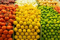 Large selection of tomatoes, lemons and limes on display in market, close-up full frame