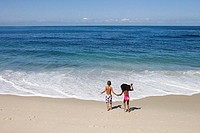 Boy and girl 5-7 holding hands on sandy beach near water's edge, Atlantic Ocean in background, rear view