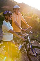 Mature couple standing with bicyles on mountain trail in bright sunlight, looking at scenery lens flare