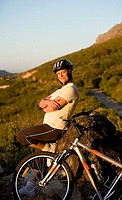 Mature woman taking break from cycling on mountain trail, standing beside rock, arms folded, side view, portrait