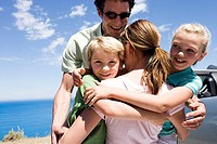 Family embracing beside parked car on clifftop overlooking Atlantic Ocean, smiling, portrait